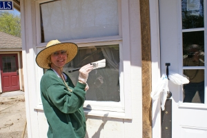 Volunteer and jeweler Linda Widmer paints the trim on the Doll  Shop windows.