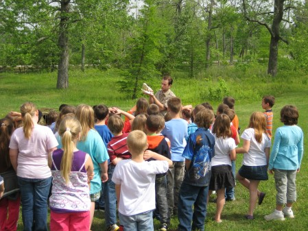 A group of students enjoys hands-on learning with a park interpreter.